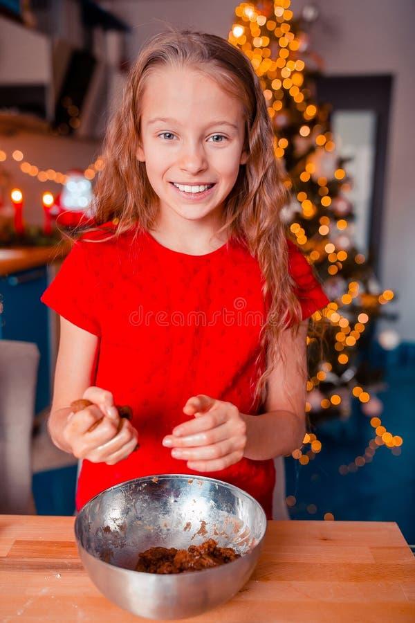 Adorable little girl baking Christmas gingerbread cookies. Adorable happy little girl baking Christmas gingerbread cookies royalty free stock photos