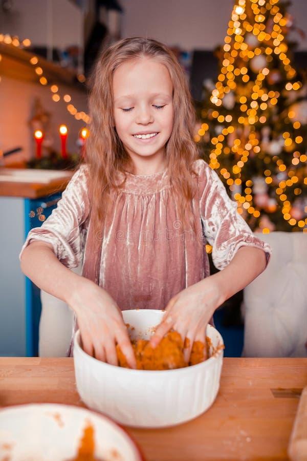 Adorable little girl baking Christmas gingerbread cookies. Adorable happy little girl baking Christmas gingerbread cookies royalty free stock photography