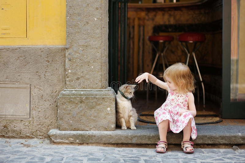 Adorable happy little girl and a cat. Outdoors