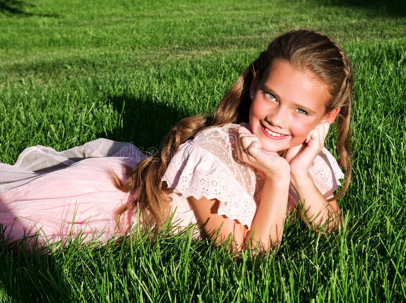 Adorable happy little girl child lying on the grass in the park on summer day stock images