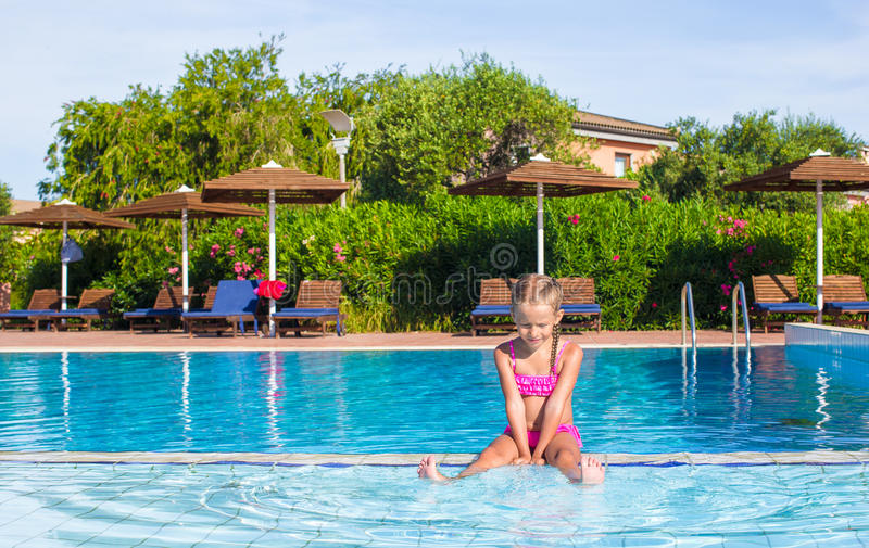 Adorable happy little girl enjoy swimming in the. Cute little girl in the swimming pool looks at camera royalty free stock photo