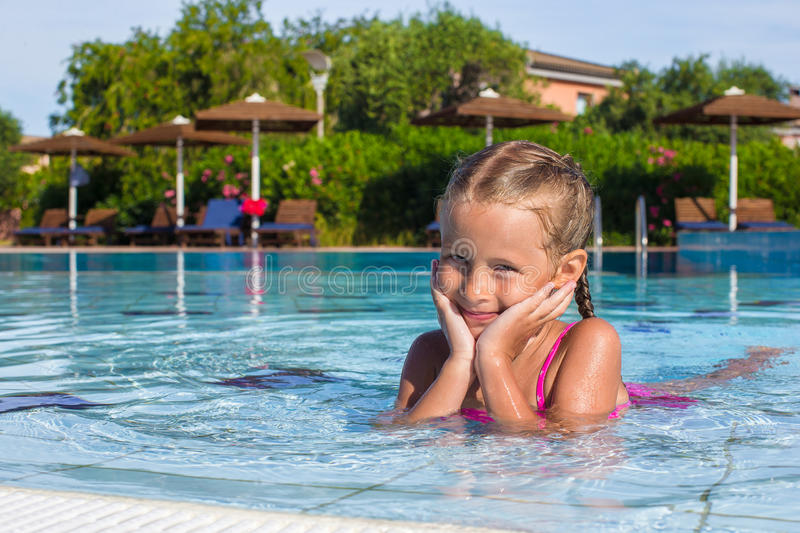 Adorable happy little girl enjoy swimming in the. Cute little girl in the swimming pool looks at camera royalty free stock photos