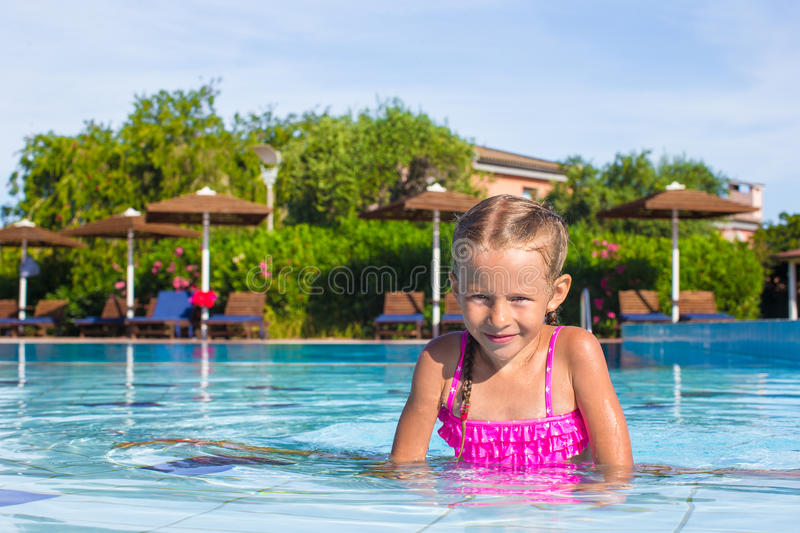 Adorable happy little girl enjoy swimming in the. Cute little girl in the swimming pool looks at camera stock photo