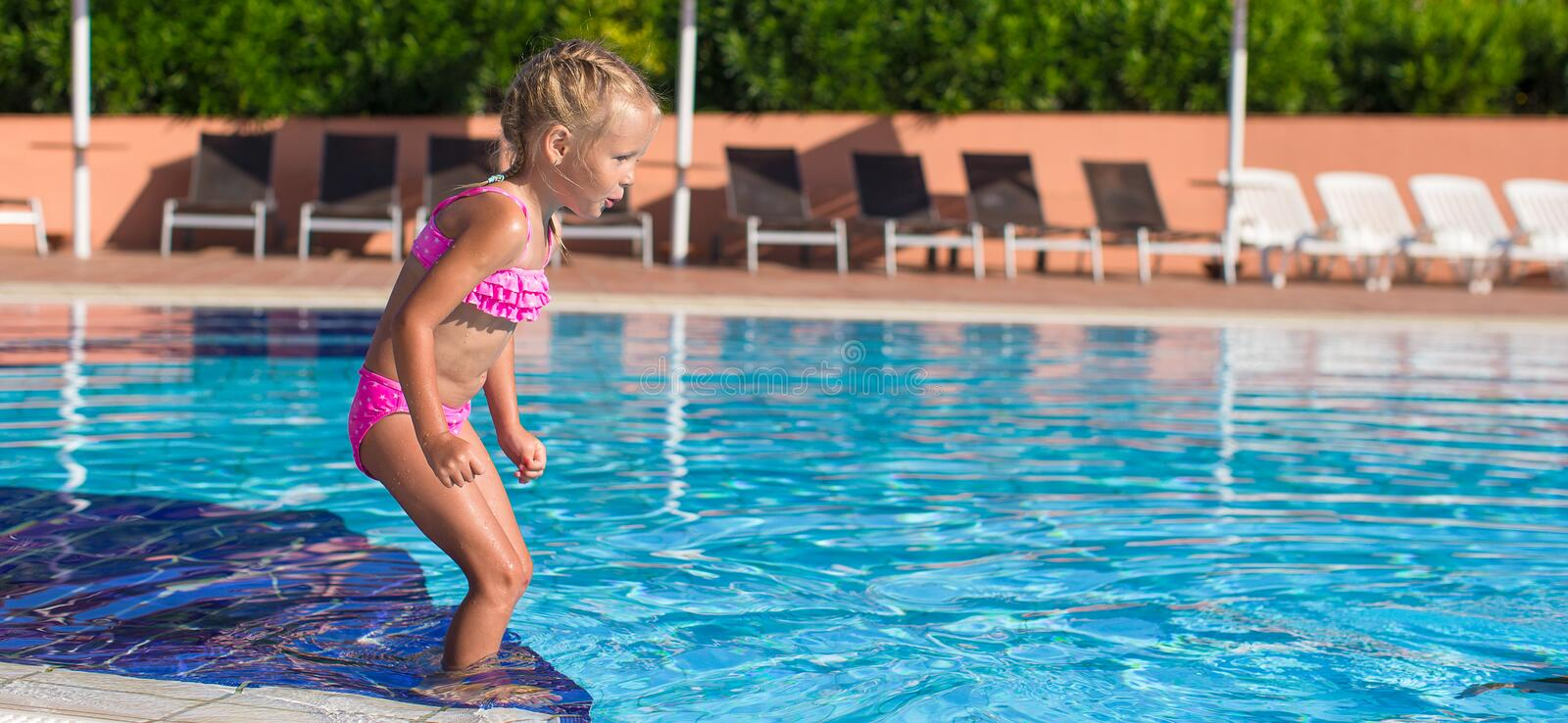 Adorable happy little girl enjoy swimming in the. Cute little girl in the swimming pool looks at camera stock photography