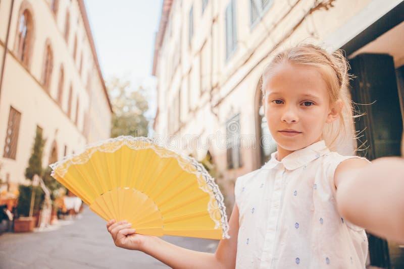 Adorable fashion little girl outdoors in European city. Adorable happy little girl taking selfie outdoors in european city. Portrait of caucasian kid enjoy royalty free stock photos
