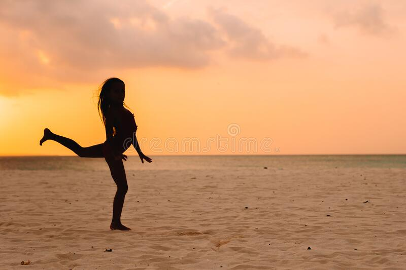 Adorable happy little girl on white beach at sunset. Adorable happy little girl on white beach at sunset stock photo