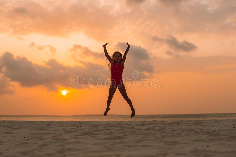 Adorable happy little girl on white beach at sunset. Adorable happy little girl on white beach at sunset royalty free stock photos