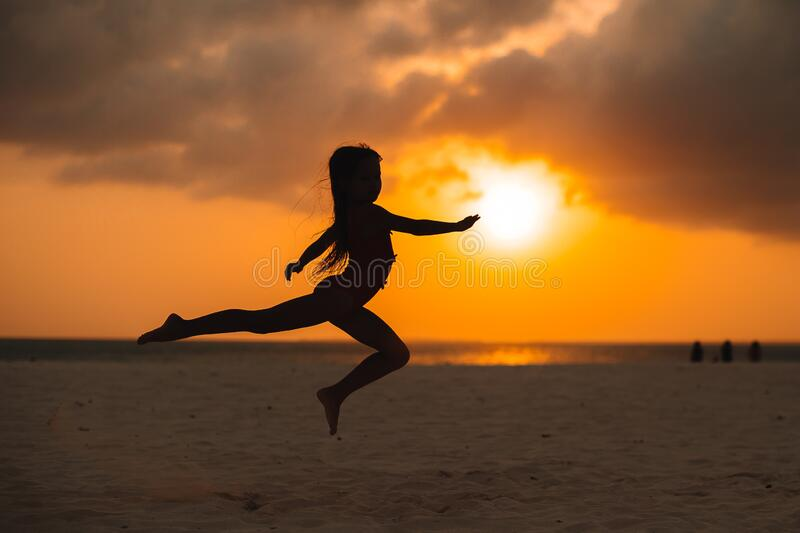 Adorable happy little girl on white beach at sunset. Adorable happy little girl on white beach at sunset stock photos