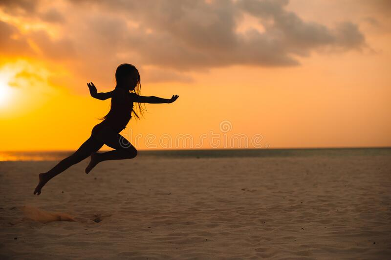 Adorable happy little girl on white beach at sunset. Adorable happy little girl on white beach at sunset royalty free stock photo