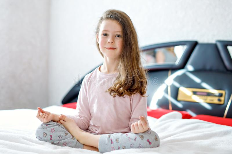 Adorable happy little kid girl after sleeping in his white bed in colorful nightwear. School child making baby yoga stock photo