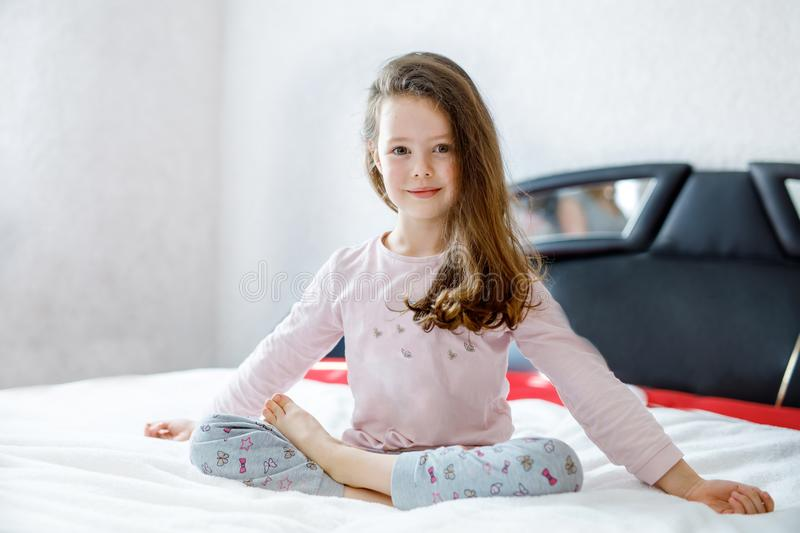 Adorable happy little kid girl after sleeping in his white bed in colorful nightwear. School child making baby yoga royalty free stock photos