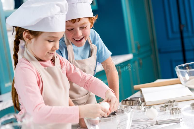 adorable happy little kids in chef hats and aprons making dough together royalty free stock image