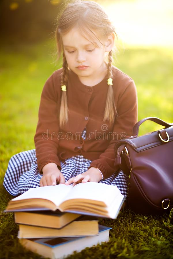 Preschool girl reading books. Little genius concept. Adorable happy little preschooler girl with pigtails ready back to school, reading textbooks outdoors royalty free stock images