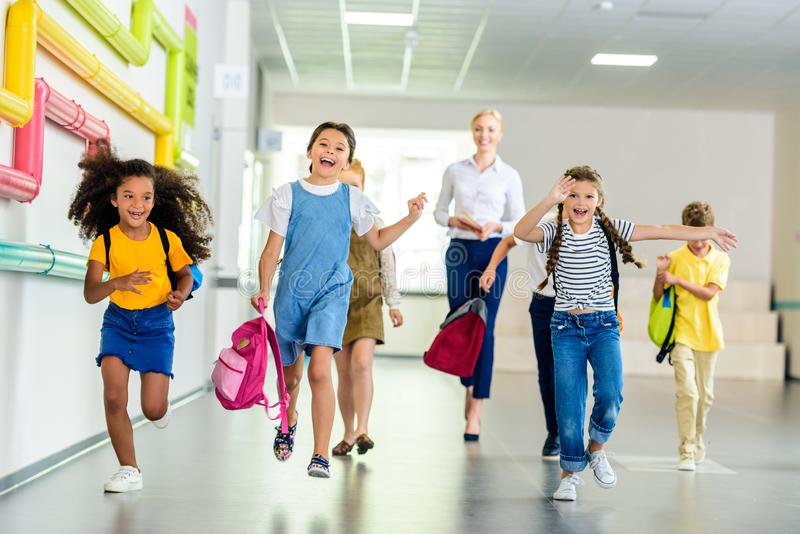adorable happy schoolchildren running by school corridor together with teacher royalty free stock photos
