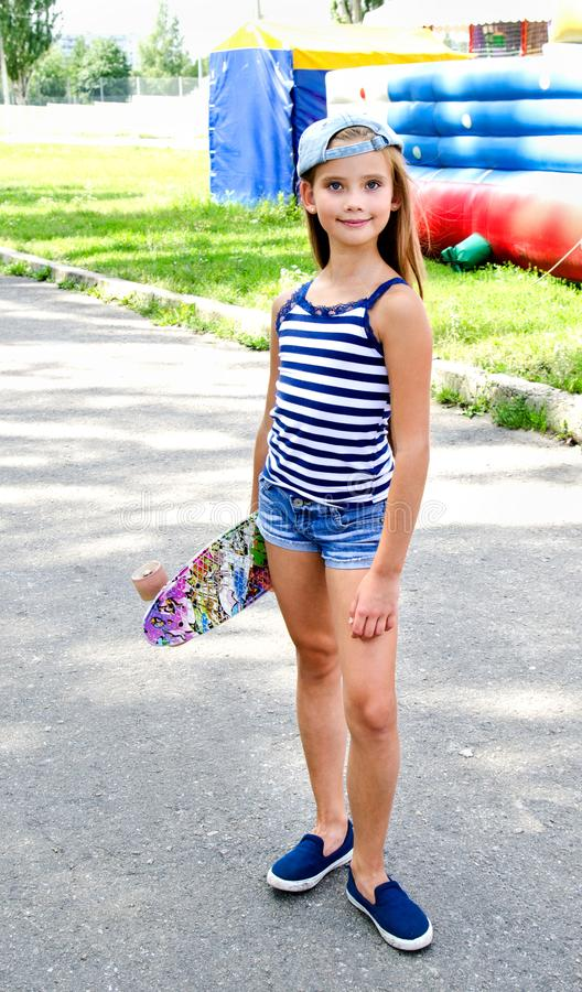 Adorable happy smiling little girl child with skateboard outdoo royalty free stock photography