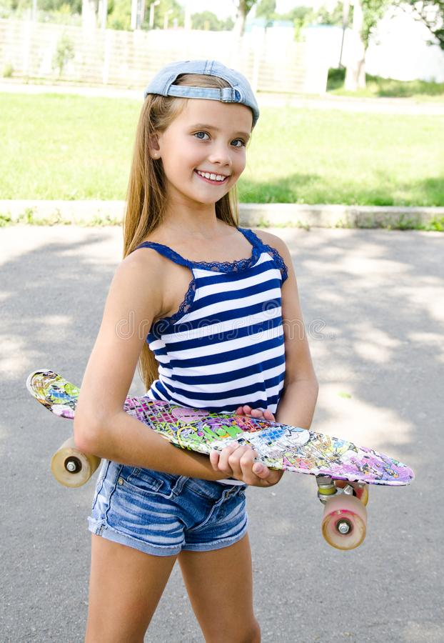 Adorable happy smiling little girl child with skateboard outdoo stock photos