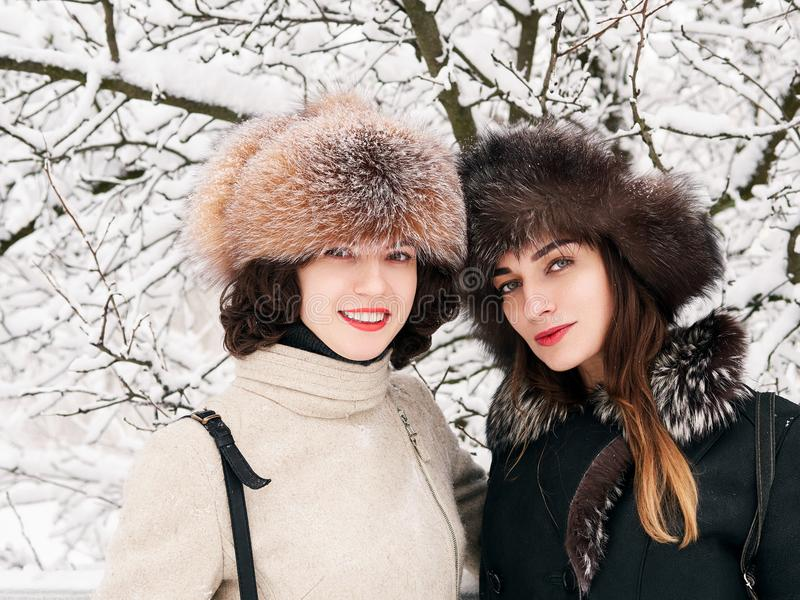 Adorable happy young brunette women girlfriends in fur hats having fun snowy winter park forest in nature royalty free stock photos
