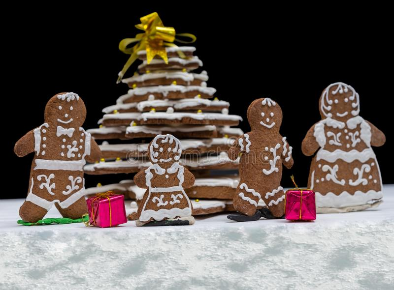 Adorable homemade gingerbread Christmas tree with cute gingerbread family with gifts on dark background. Mockup for seasonal offers and holiday post card stock photo