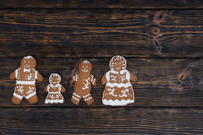 Adorable homemade gingerbread family on dark wooden background. Mockup for seasonal offers and holiday post card stock image