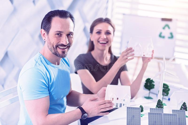 Emotional eco engineers smiling and showing their futuristic eco houses stock image