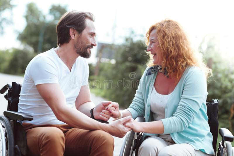 Adorable husband and wife in wheelchairs holding hands together stock photography