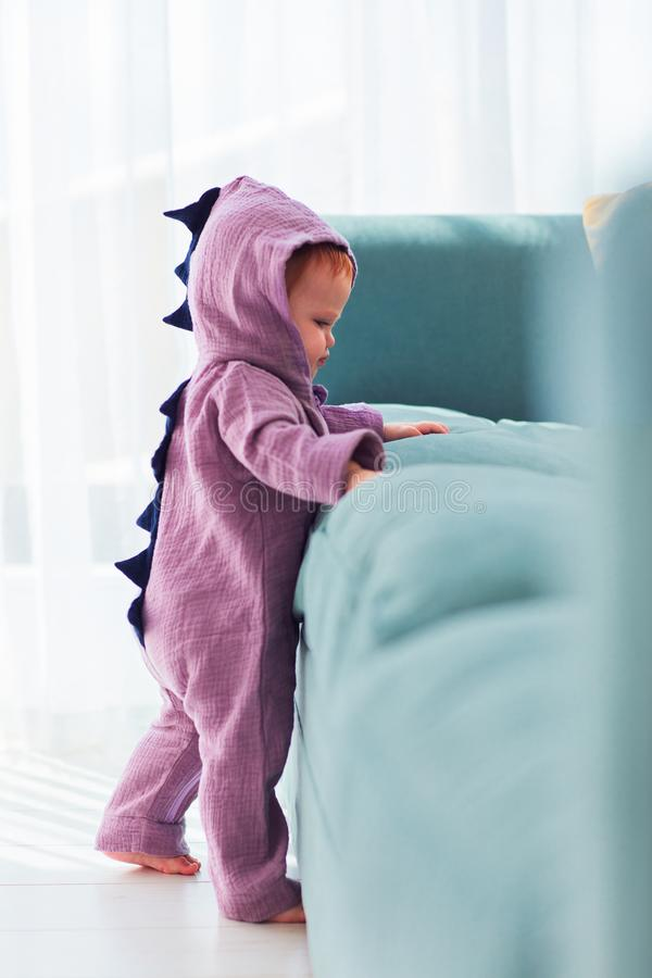 Adorable infant baby girl in cute dinosaur costume is standing near the sofa. Adorable infant baby girl wearing cute dinosaur costume is standing near the sofa stock photography