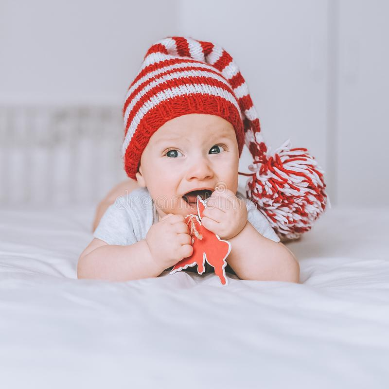 adorable infant child in red and white striped hat with pompom playing with toy angel royalty free stock photo