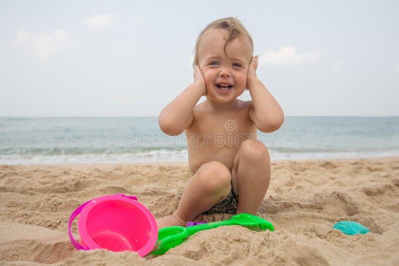 Adorable infant on sandy beach stock photo