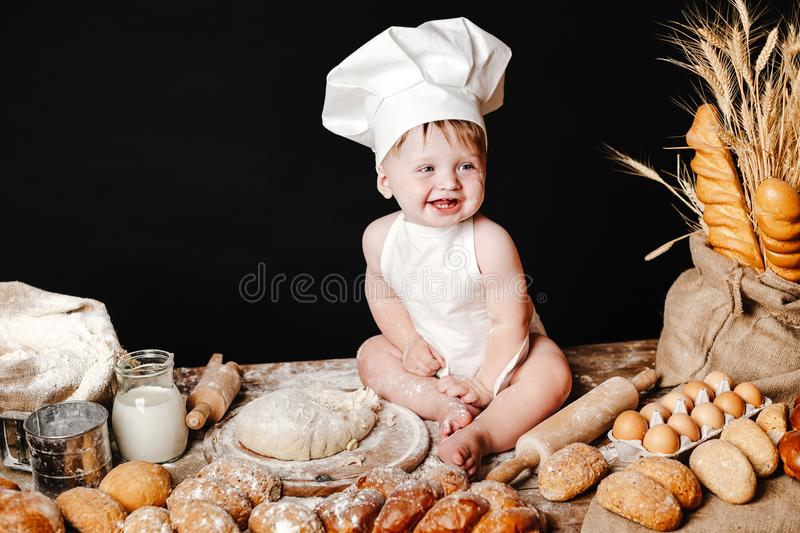 Adorable infant on table with dough. Charming toddler baby in hat of cook and apron sitting on table with bread loaves and cooking ingredients laughing happily royalty free stock photo