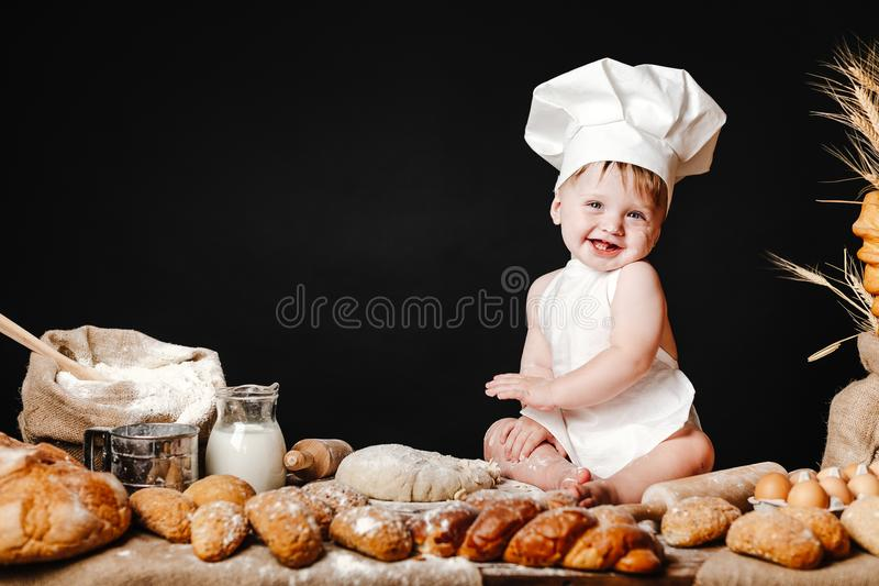 Adorable infant on table with dough. Charming toddler baby in hat of cook and apron sitting on table with bread loaves and cooking ingredients laughing happily stock photography