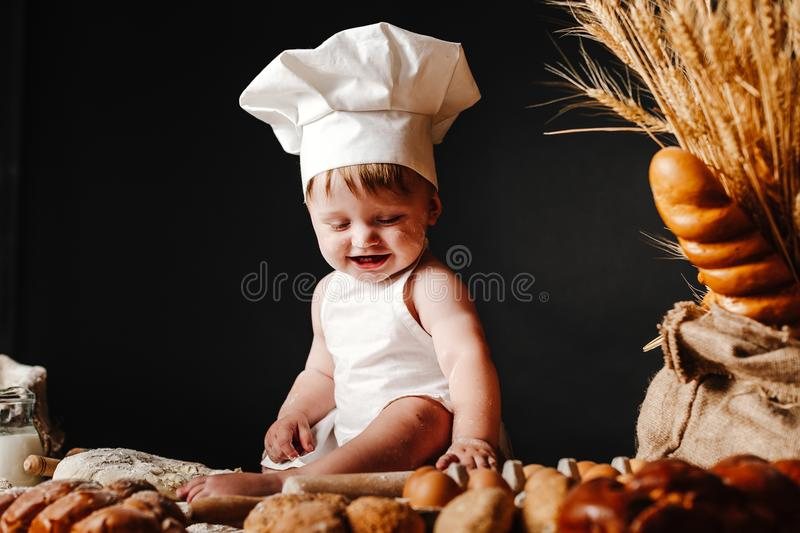 Adorable infant on table with dough. Charming toddler baby in hat of cook and apron sitting on table with bread loaves and cooking ingredients laughing happily stock photo