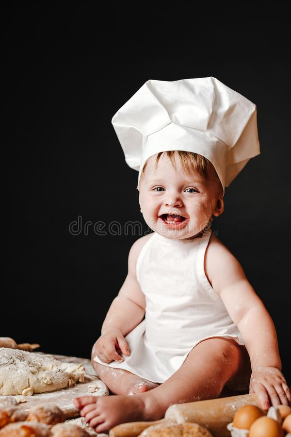 Adorable infant on table with dough. Charming toddler baby in hat of cook and apron sitting on table with bread loaves and cooking ingredients laughing happily stock images