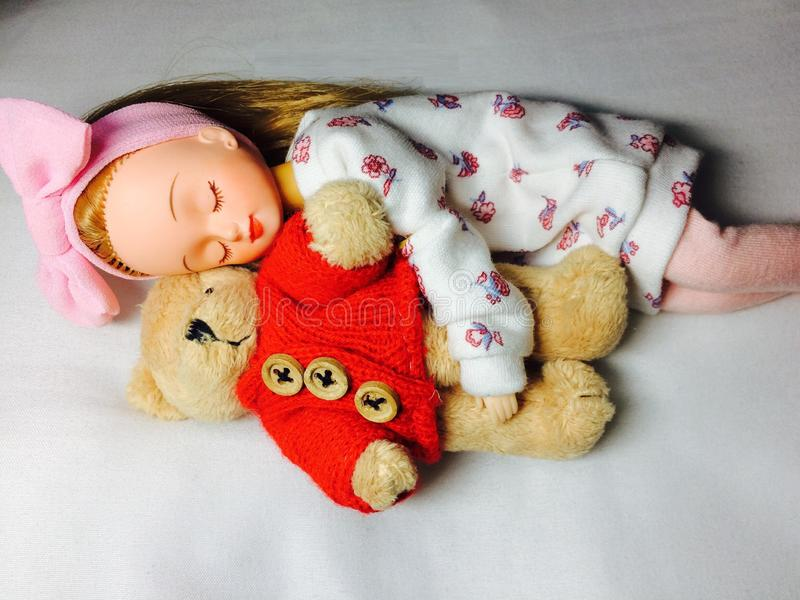 An adorable Japanese doll is sleeping with her teddy bear. royalty free stock photos