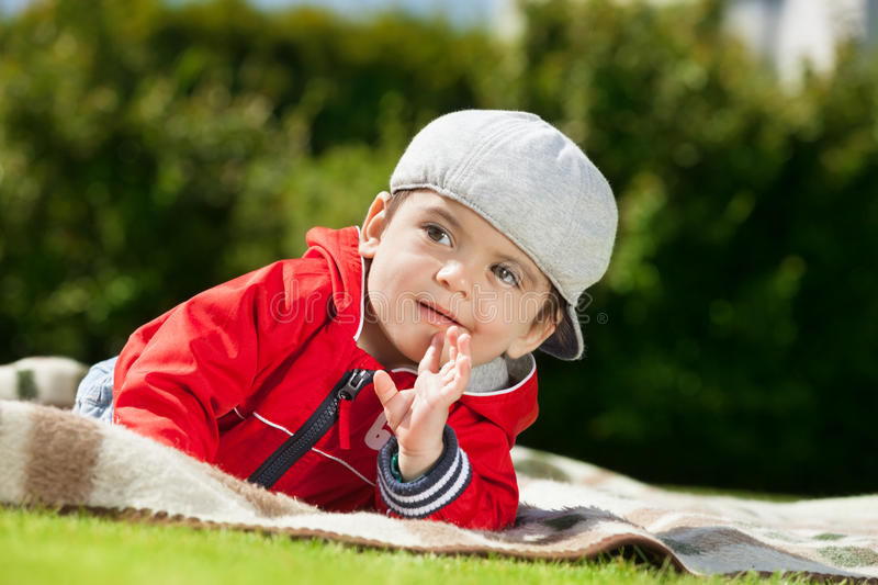 Adorable kid. Adorable arabic kid laying on the plaid royalty free stock photo