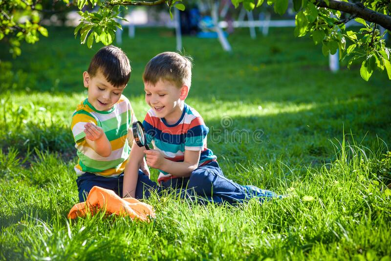 Adorable kid boy making fire on paper with a magnifying glass outdoors, on sunny day stock image
