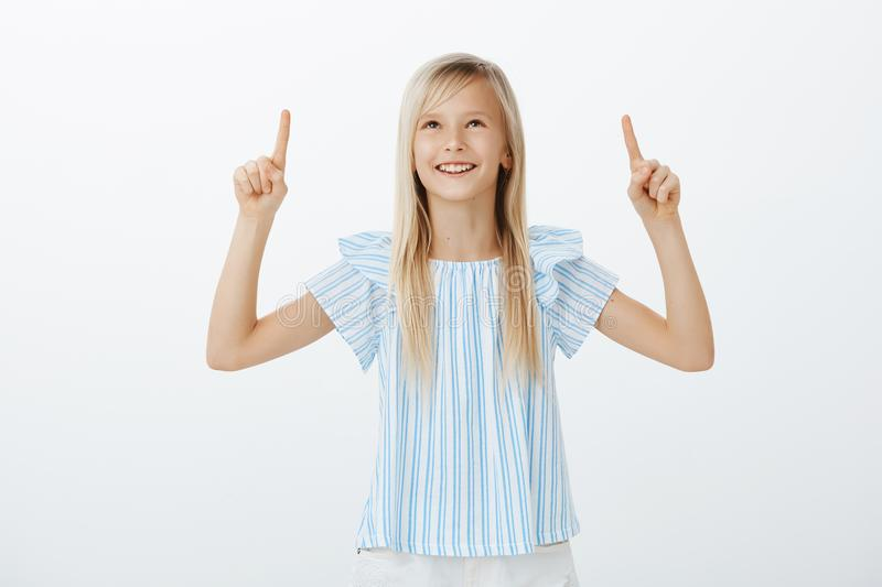 Adorable kid discussing cloud shapes with friend. Portrait of creative happy young girl with blond hair, smiling broadly royalty free stock photos