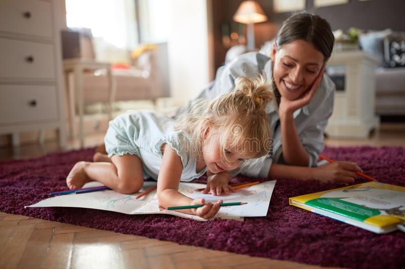 Adorable kid with female drawing indoor stock photography