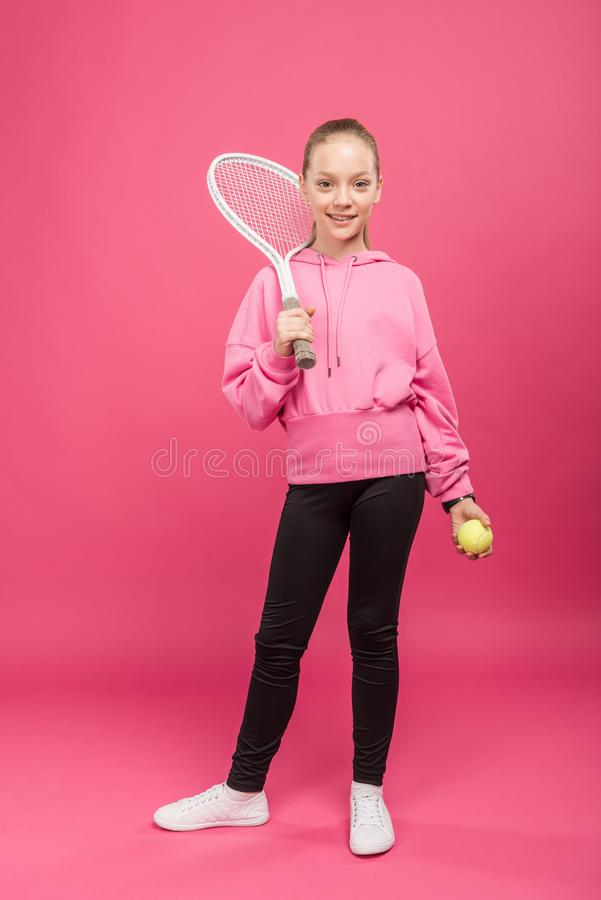 Adorable kid posing with tennis racket and ball, isolated. On pink stock photo
