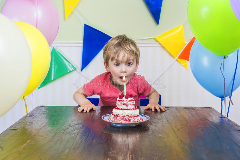 Adorable kid's birthday party. Adorable kid blowing out the candle on his birthday cake stock photo