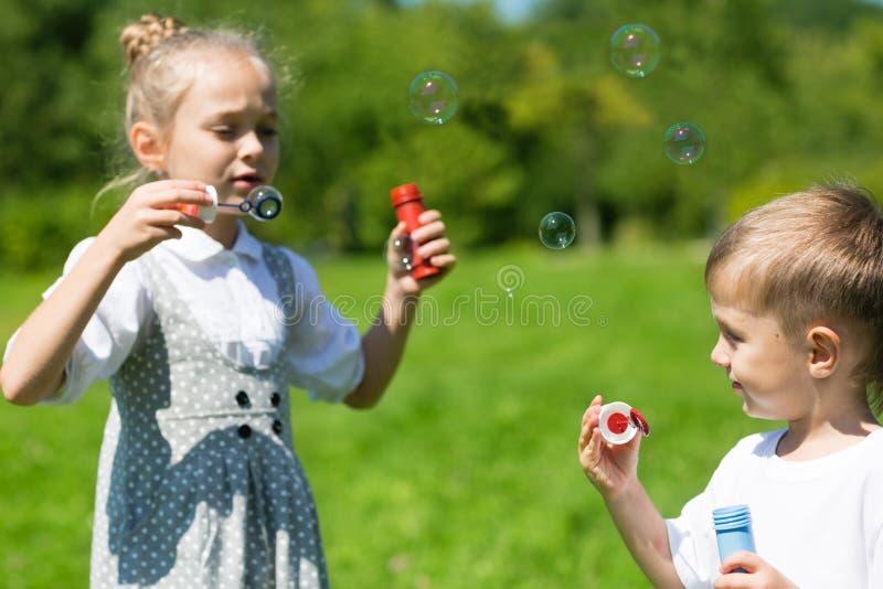 Adorable kids blow bubbles outdoors stock photo