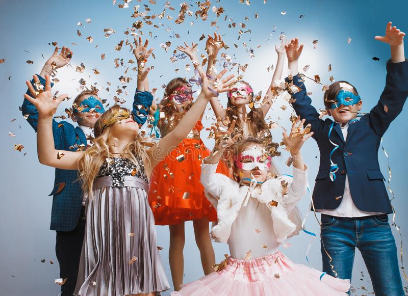 Adorable kids have fun together, throw colourful confetti, stock image