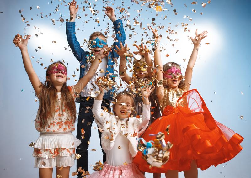 Adorable kids have fun together, throw colourful confetti, royalty free stock image