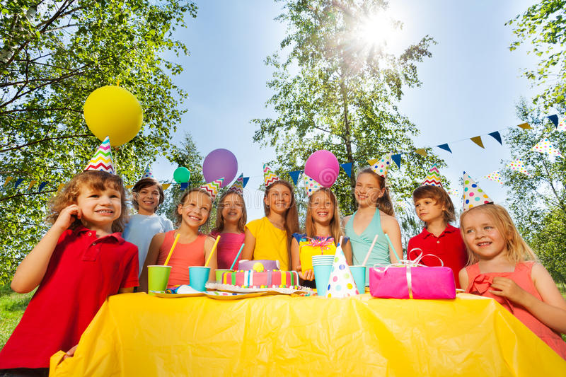Adorable kids having fun at the birthday party. Big group of happy age-diverse kids standing in a row next to the birthday cake at the outdoor party stock image