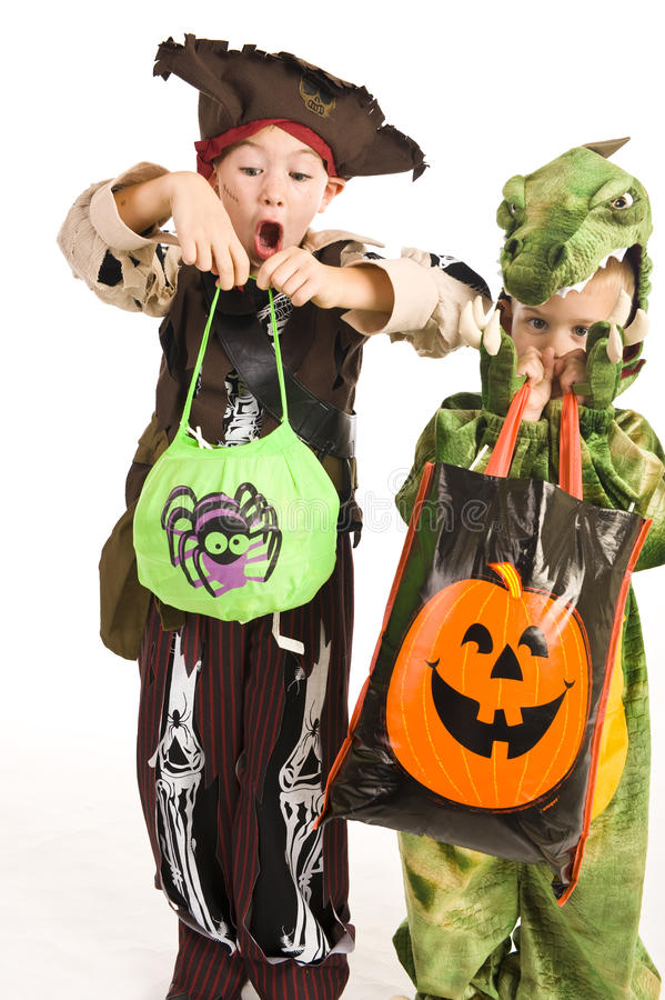 Adorable kids playing trick or treat. Kids in Halloween costumes playing trick or treat and holding bags full of candy royalty free stock image