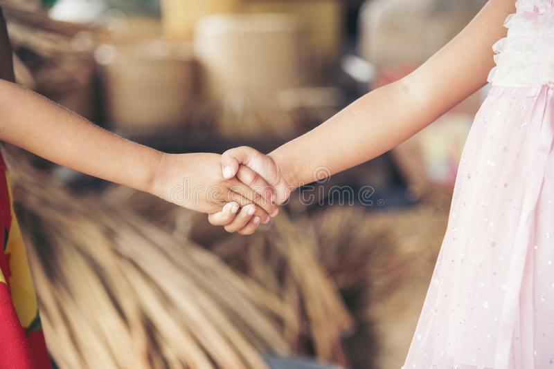 Adorable kids shaking hands together stock photos