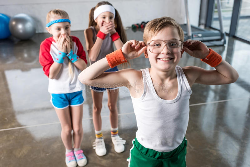 Adorable kids in sportswear fooling around at fitness studio stock photography