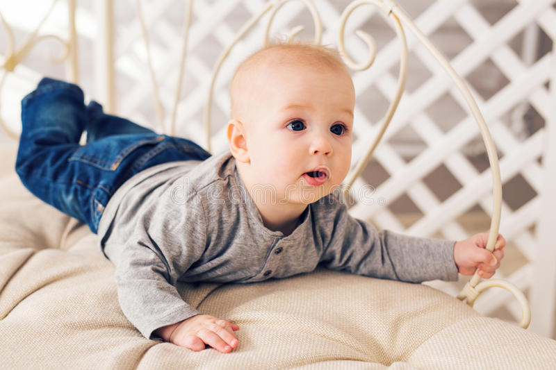 Adorable laughing baby boy in sunny bedroom. Newborn child relaxing. Family morning at home. Little kid lying on tummy. Adorable baby boy in sunny bedroom stock images