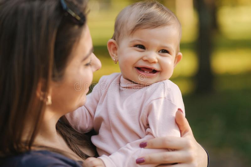 Adorable laughing baby girl on mom`s hands in autumn park. Close up on mother and daughter. Happy family royalty free stock photos