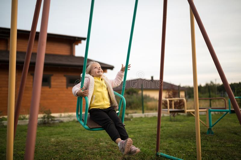 Adorable laughing little girl on swing in summer day. Happy children day concept. Kid playing outdoor on backyard stock photos