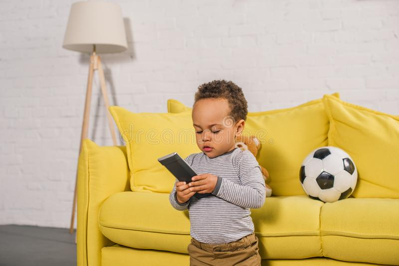 Adorable little african american child holding remote controller. At home stock photo